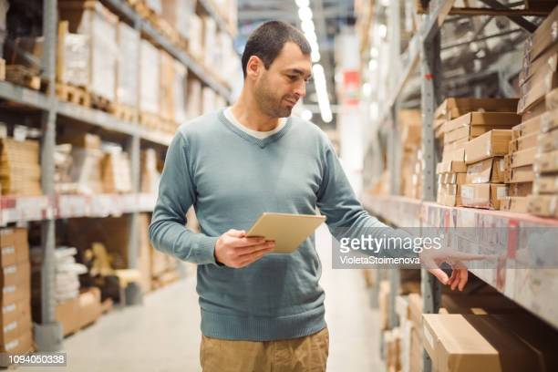 manager doing stocktaking of product in warehouse - top garment stock pictures, royalty-free photos & images