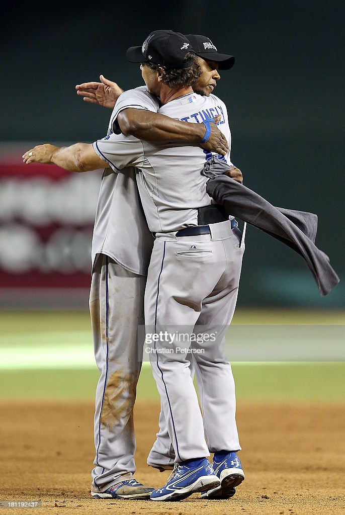 Manager Don Mattingly #8 and Hanley Ramirez #13 of he Los Angeles Dodgers hug in celebration after defeating the Arizona Diamondbacks to clinch the National League West title and a postseason berth at Chase Field on September 19, 2013 in Phoenix, Arizona.