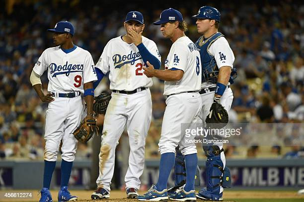 Manager Don Mattingly meets on the mound after relieving Clayton Kershaw in the seventh inning of Game One of the National League Division Series...