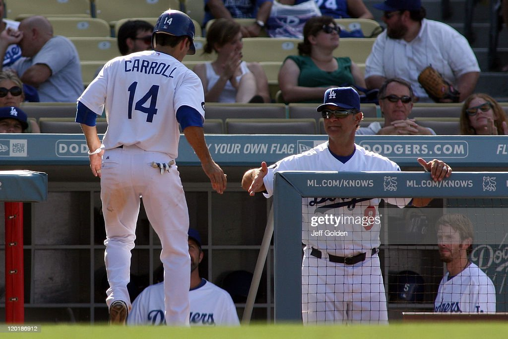 Manager Don Mattingly #8 of the Los Angeles Dodgers congratulates Jamey Carroll #14 after Carroll scored against the Arizona Diamondbacks in the ninth inning of the game at Dodger Stadium on July 31, 2011 in Los Angeles, California.