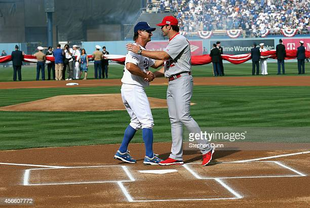 Manager Don Mattingly of the Los Angeles Dodgers greets manager Mike Matheny outfield the St Louis Cardinals at home plate before Game One of the...