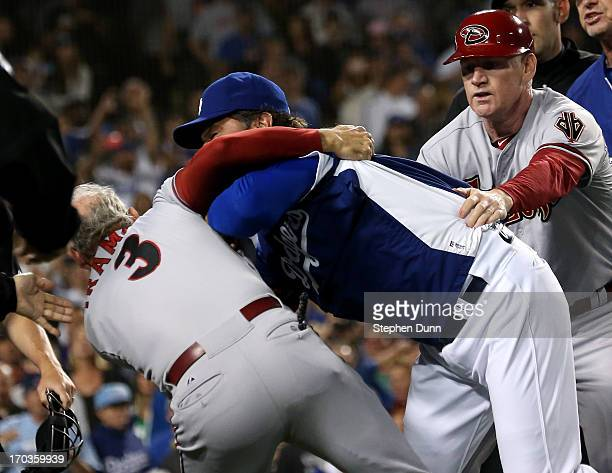 Manager Don Mattingly of the Los Angeles Dodgers pushes down coach Alan Trammell of the Arizona Diamondbacks during as Diamondbacks coach Matt...