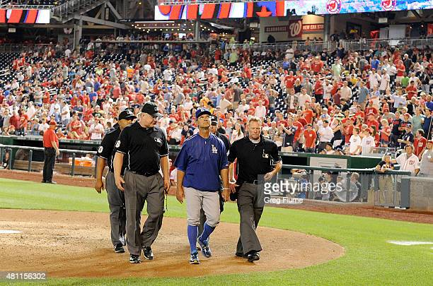 Manager Don Mattingly of the Los Angeles Dodgers walks off the field with the umpire crew after the third power outage of the game before the sixth...