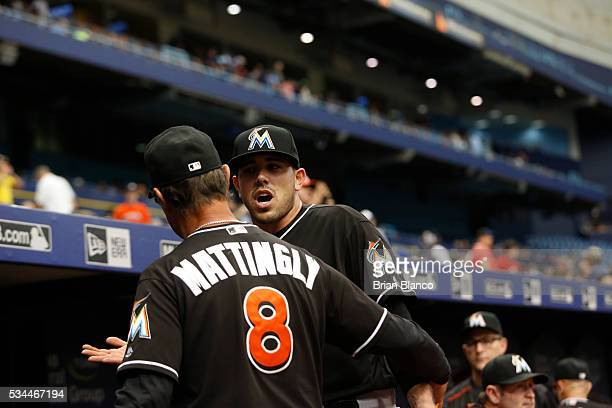 Manager Don Mattingly of the Miami Marlins guides pitcher Jose Fernandez into the dugout after coming out to separate Fernandez from a verbal...