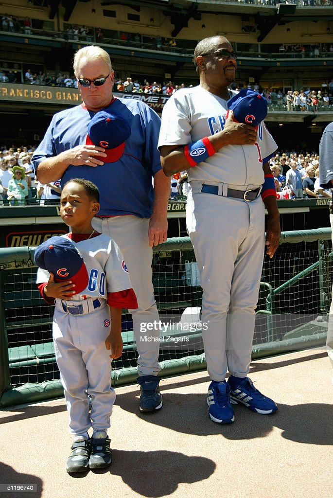 Manager Dusty Baker #12 of the Chicago Cubs and his son, Darren Baker, listen to the National Anthem with bench coach Dick Pole #46 before the MLB game against the San Francisco Giants at SBC Park on August 7, 2004 in San Francisco, California. The Cubs defeated the Giants 8-4 for Greg Maddux' 300th career win.