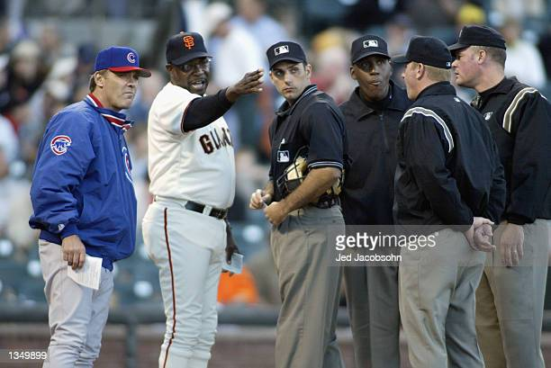 Manager Dusty Baker of the San Francisco Giants has a discussion with manager Bruce Kimm of the Chicago Cubs and umpires Justin Klemm Chuck...