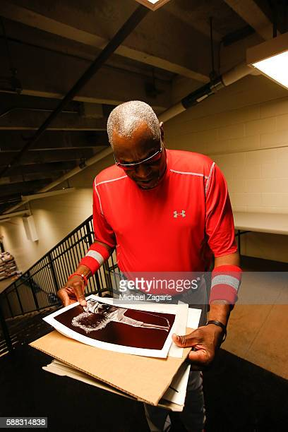 Manager Dusty Baker of the Washington Nationals looks at photos of Roger Daltrey from The Who prior to the game against the San Francisco Giants at...