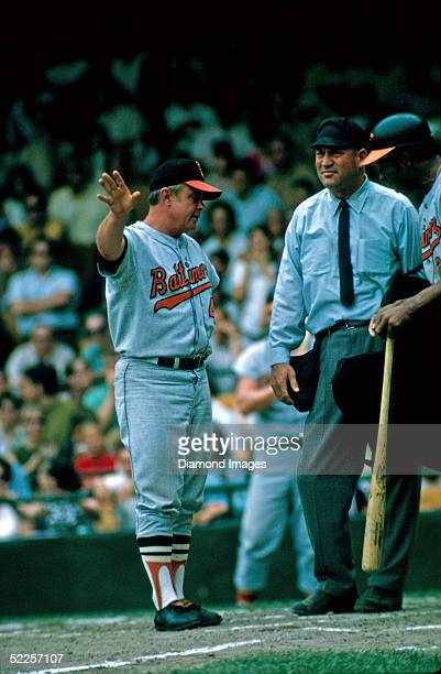 Manager Earl Weaver of the Baltimore Orioles has a discussion with the home plate umpire while Frank Robinson waits to bat during a 1969 game against...