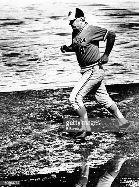 Manager Earl Weaver of the Baltimore Orioles jogs through the water on the field as rain forces the postponment of Game 1 of the 1979 World Series...