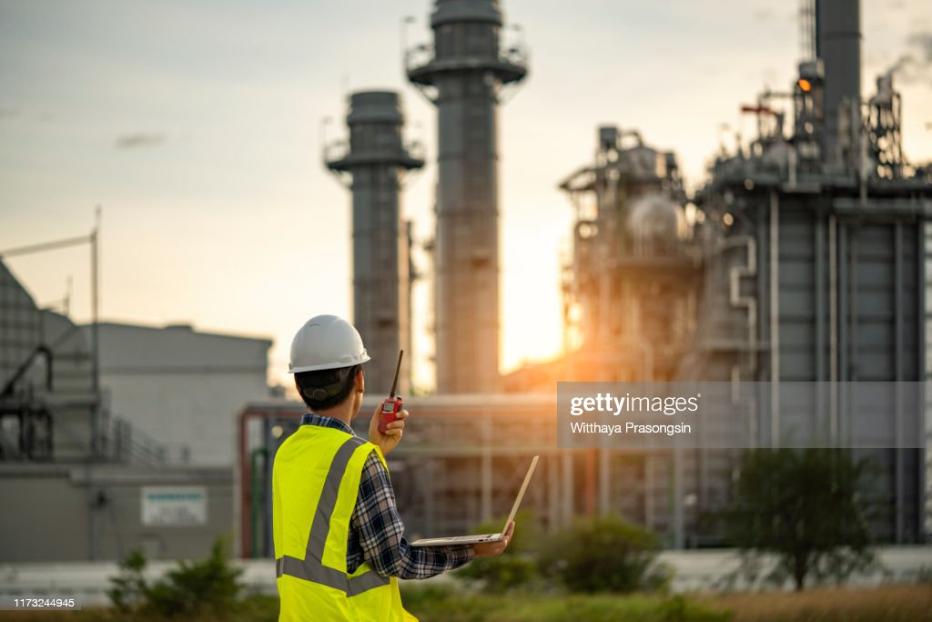 Manager Engineering in standard safety uniform working in gas turbine electric power plant during sunset or morning time background : Stock Photo