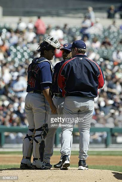 Manager Eric Wedge of the Cleveland Indians meets on the mound with catcher Victor Martinez and third baseman Jose Hernandez during the game between...