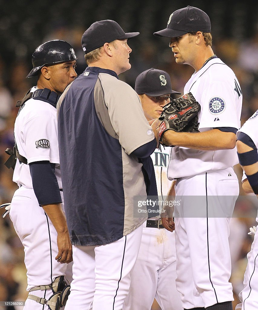 Manager Eric Wedge #22 talks to relief pitcher Tom Wilhelmsen #54 before removing him from the game in the fifth inning against the Toronto Blue Jays at Safeco Field on August 16, 2011 in Seattle, Washington.