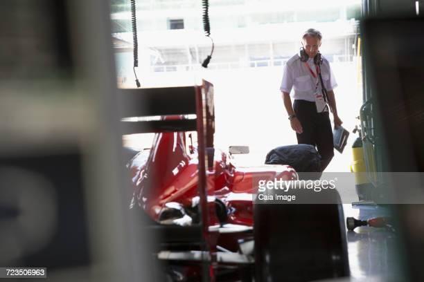 Manager examining formula one race car in repair garage