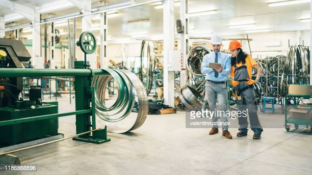 manager explaining to female worker at factory - sales occupation stock pictures, royalty-free photos & images