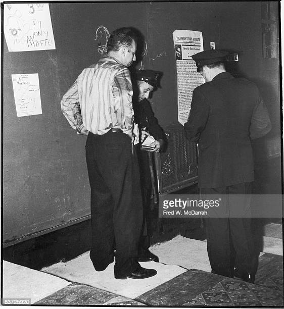 Manager Frank LoPiccolo of the Cavern Cafe stands with his hands in his pockets as Sixth Precinct Office George Parker issues him a summons for...