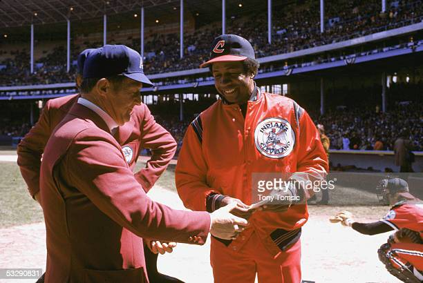 Manager Frank Robinson submits his lineup to an unidentified umpire before an MLB game at Cleveland Municipal Stadium in Cleveland, Ohio. Frank...