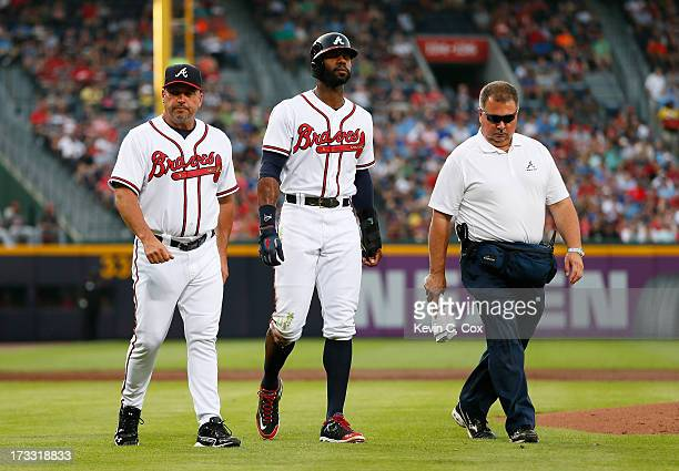 Manager Fredi Gonzalez and trainer Jim Lovell walk Jason Heyward of the Atlanta Braves off the field after he injured himself sliding into third base...