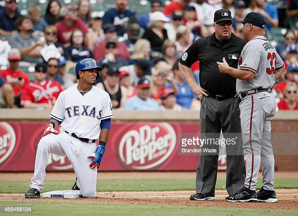 Manager Fredi Gonzalez of the Atlanta Braves argues to third base umpire Bill Miller that Luis Sardinas of the Texas Rangers should be out during the...