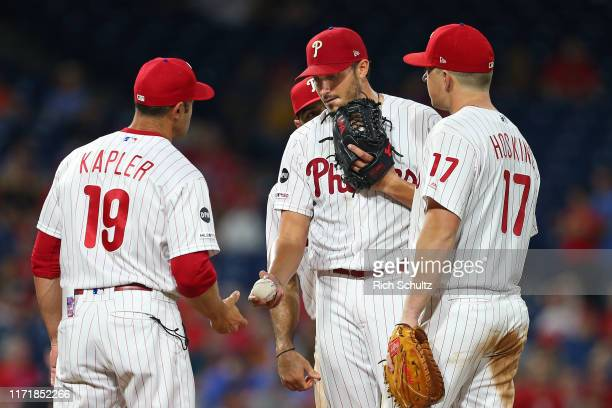 Manager Gabe Kapler of the Philadelphia Phillies takes the ball from starting pitcher Zach Eflin as Cesar Hernandez and Rhys Hoskins look on against...