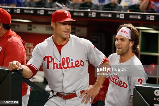 Manager Gabe Kapler of the Philadelphia Phillies talks with Bryce Harper during the first inning of the MLB game against the Arizona Diamondbacks at...