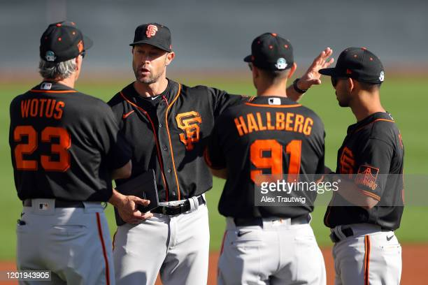 Manager Gabe Kapler speaks with third base coach Ron Wotus, assistant coach Mark Hallberg, and infield coach Kai Correa of the San Francisco Giants...