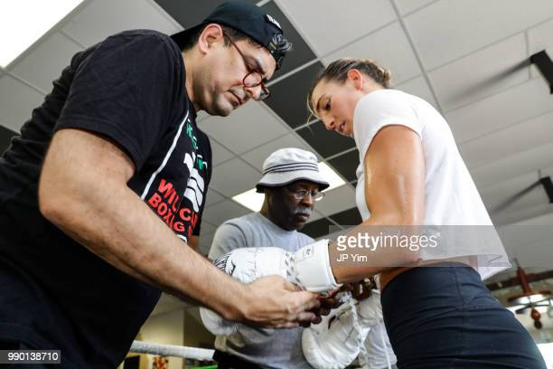 Manager George Ruiz and trainer Al Mitchell help take the gloves off boxer Mikaela Mayer as she wraps up her media workout at Azteca Gym on June 27...