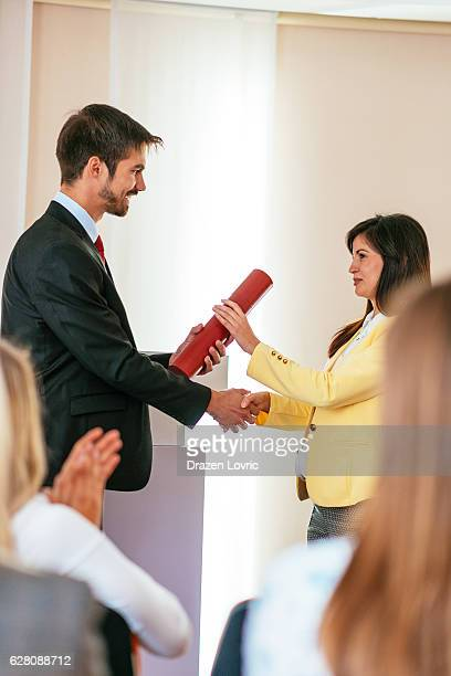 Manager gives certificate to one of his employees