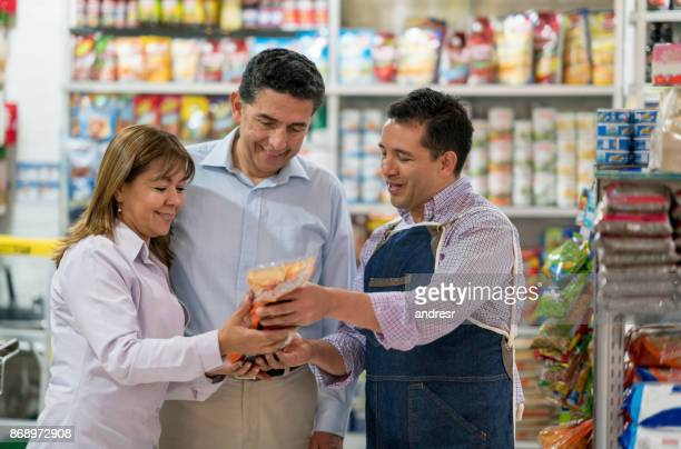 Manager helping a couple at the grocery shop