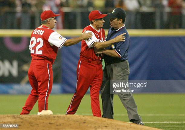 Manager Higinio Velez of Cuba is restrained by the umpire during a game against Puerto Rico on March 15 2006 at Hiram Bithorn Stadium in San Juan...