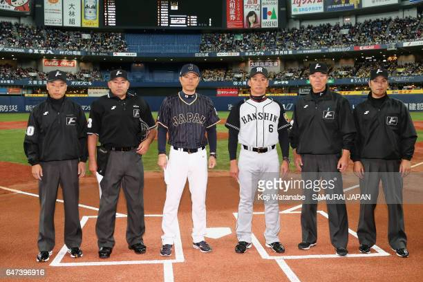 Manager Hiroki Kokubo of Japan and manager Tomoaki Kanemoto pose with umpires prior to the World Baseball Classic WarmUp Game between Japan and...