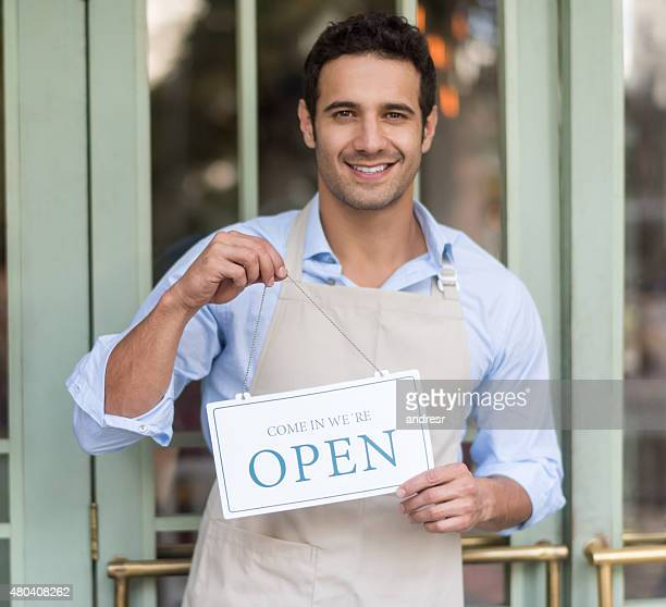 Manager holding an open sign outside a shop