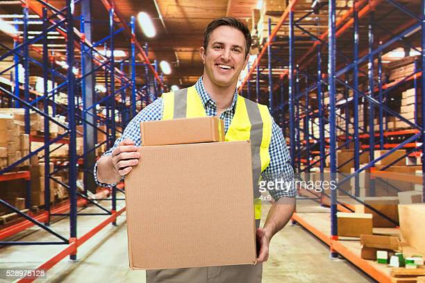 Manager holding box in warehouse