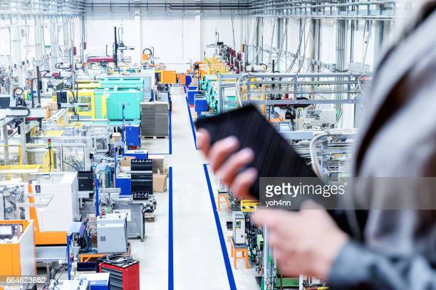 Manager holding tablet, focus on robotic machines
