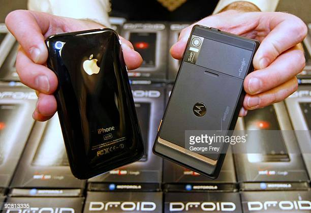 A manager holds an Apple iPhone and Motorola's new Droid smart phone sold through Verizon at the Verizon store November 5 2009 in Orem Utah The...