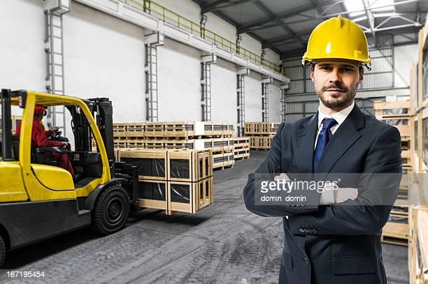 Manager, Inspector, Owner standing against forklift inside industry distribution warehouse