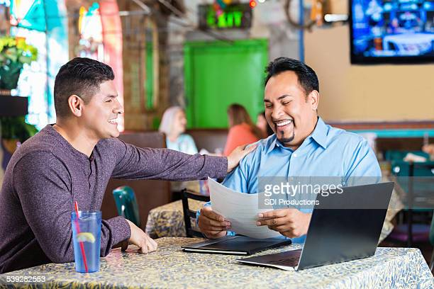 Manager interviewing potential employee for job in restaurant