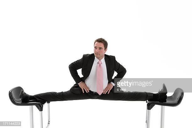 manager is caught between two chairs - split acrobatiek stockfoto's en -beelden
