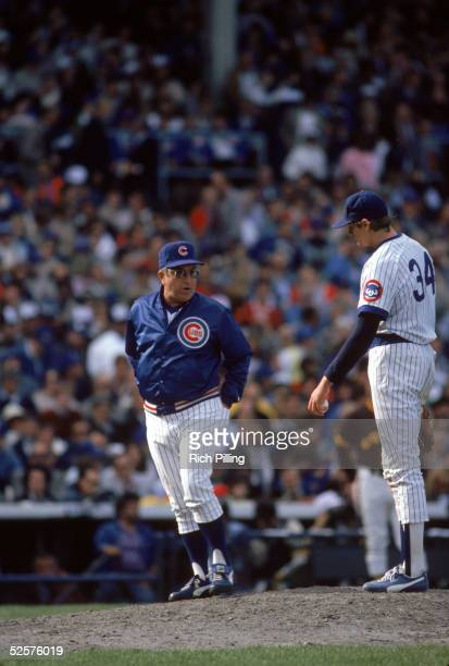 Manager Jim Frey of the Chicago Cubs talks to his pitcher Steve Trout at the mound during a game in October of 1984 at Wrigley Field in Chicago...