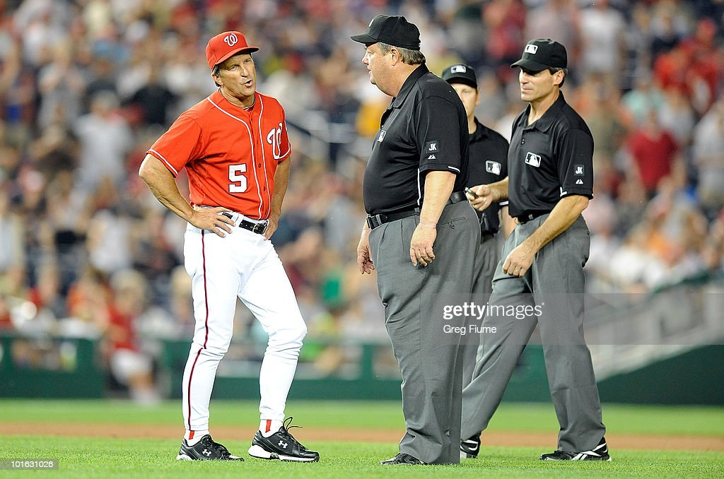 Manager Jim Riggleman of the Washington Nationals argues with first base umpire Joe West, second base umpire Angel Hernandez and third base umpire Paul Schrieber after a call in the seventh inning of the game against the Cincinnati Reds at Nationals Park on June 4, 2010 in Washington, DC.