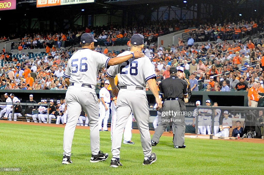 Manager Joe Girardi #28 of the New York Yankees and Buck Showalter #26 of the Baltimore Orioles walk towards home plate umpire Ed Hickox during an altercation in the first inning at Oriole Park at Camden Yards on September 9, 2013 in Baltimore, Maryland.