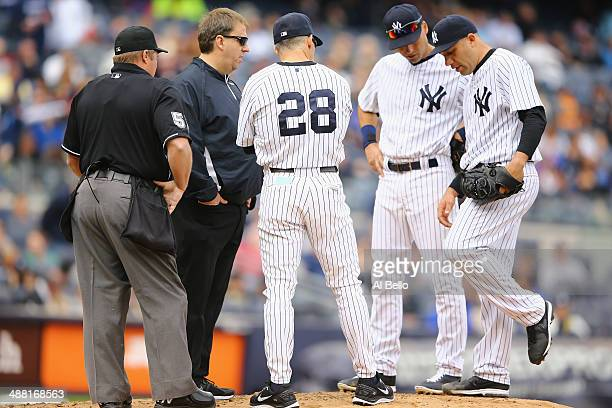 Manager Joe Girardi of the New York Yankees and Derek Jeter look at Alfredo Aceves who appears to have an injury to his leg in the fifth inning of...