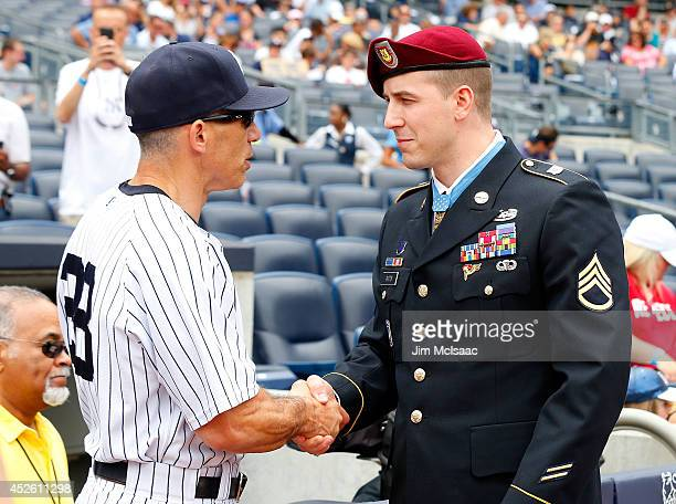 Manager Joe Girardi of the New York Yankees greets Medal of Honor recipient Staff Sergeant Ryan M Pitts before a game against the Texas Rangers at...