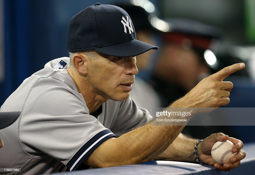 Manager Joe Girardi #28 of the New York Yankees looks on from the dugout during MLB game action against the Toronto Blue Jays on August 26, 2013 at Rogers Centre in Toronto, Ontario, Canada.