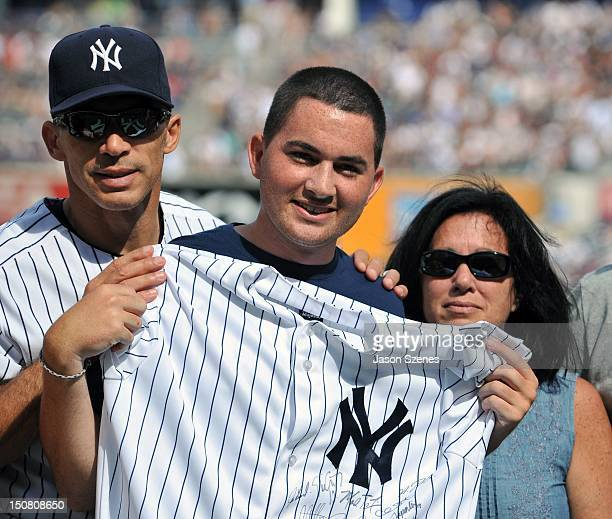 Manager Joe Girardi of the New York Yankees poses with heart transplant recipient Colby Salerno and his mother Kelly Salerno after presenting a team...
