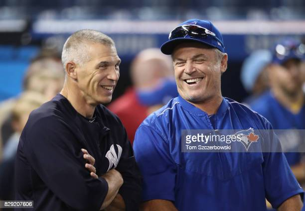 Manager Joe Girardi of the New York Yankees shares a laugh with manager John Gibbons of the Toronto Blue Jays during batting practice before the...