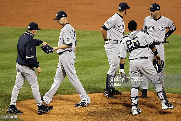Manager Joe Girardi of the New York Yankees takes starting pitcher A.J. Burnett out of the game in the bottom of the third inning against the...