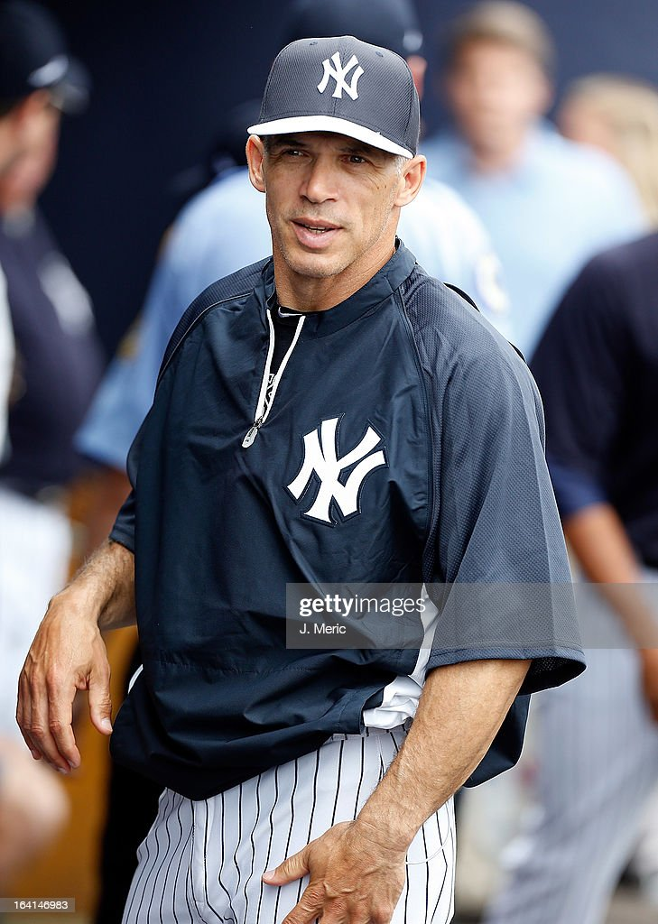 Manager Joe Girardi #28 of the New York Yankees talks with a player during a Grapefruit League Spring Training Game against the Boston Red Sox at George M. Steinbrenner Field on March 20, 2013 in Tampa, Florida.