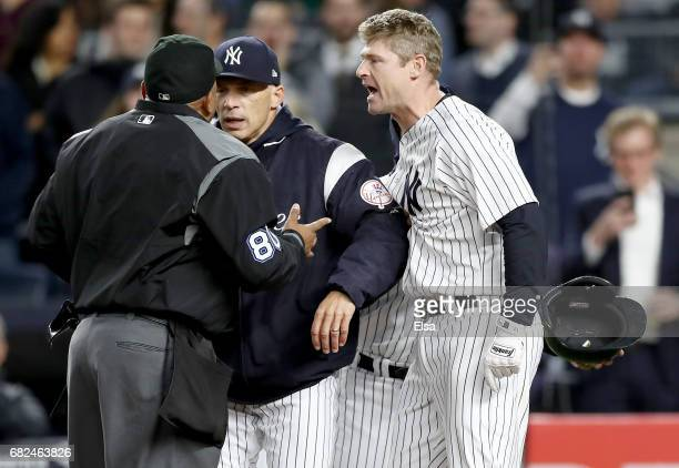 Manager Joe Girardi of the New York Yankees tries to separate home plate umpire Adrian Johnson and Chase Headley in the seventh inning against the...