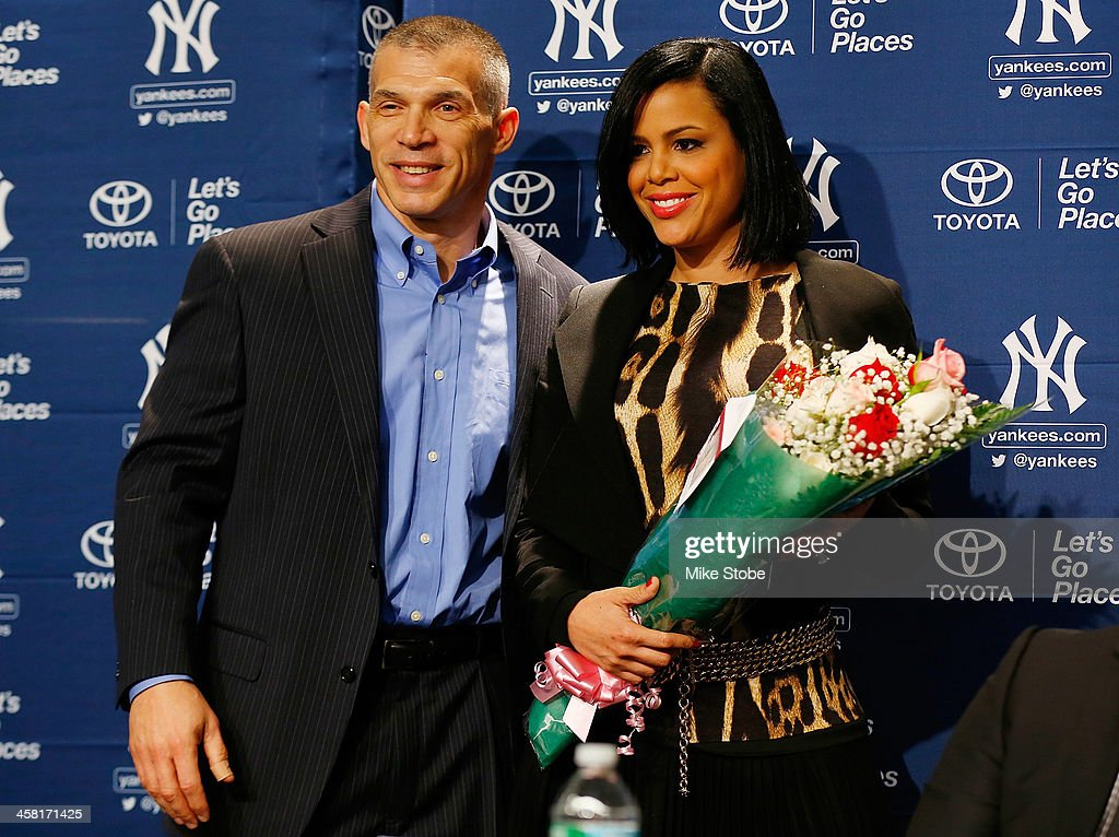 Manager Joe Girardi presents Carlos Beltrans wife Jessica with a gift during Beltran's introductory press conference at Yankee Stadium on December 20, 2013 in the Bronx borough of New York City.