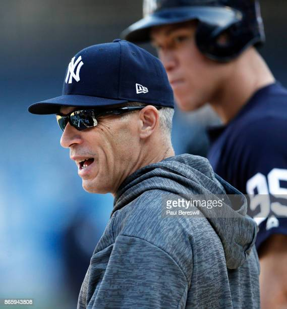 Manager Joe Girardi talks with teammates near the batting cage as Aaron Judge of the New York Yankees looks on at batting practice before game 5 of...
